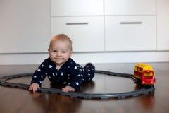 Behandla som ett barn lite pojken och att spela med drevet och resa med tåg hemma Royaltyfria Foton
