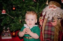 Behandla som ett barn lite pojken sitter under den dekorerade julgranen med jultomten Arkivbild