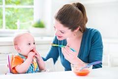 Behandla som ett barn lite pojken som äter hans första fasta mat Royaltyfri Foto