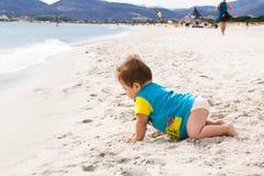 Behandla som ett barn lite pojken som bär den blåa överilade vaktdräkten som spelar på den tropiska havstranden UV och solskydd f Arkivfoto