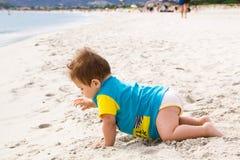 Behandla som ett barn lite pojken som bär den blåa överilade vaktdräkten som spelar på den tropiska havstranden UV och solskydd f Royaltyfria Foton