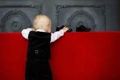 Behandla som ett barn lite pojken som försöker att bära skor för patenterat läder Royaltyfri Bild