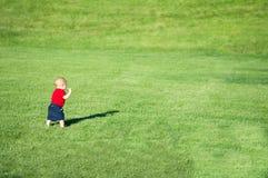 Behandla som ett barn lite pojken som går i ett fält Arkivfoton