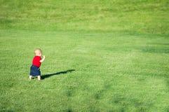Behandla som ett barn lite pojken som går i ett fält Royaltyfri Foto