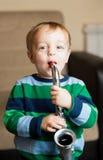 Behandla som ett barn lite pojken som leker en saxofon Fotografering för Bildbyråer