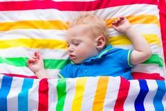 Behandla som ett barn lite pojken som sover i säng Arkivfoto
