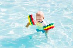 Behandla som ett barn lite pojken som spelar i simbassäng arkivfoto