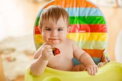 Behandla som ett barn lite pojkesammanträde i en ljus stol som äter jordgubbar royaltyfri fotografi