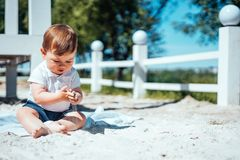 Behandla som ett barn lite pojkesammanträde på sanden Royaltyfria Bilder