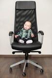 Behandla som ett barn lite pojkesammanträde på stor stol Fotografering för Bildbyråer