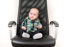 Behandla som ett barn lite pojkesammanträde på stor stol Arkivfoton