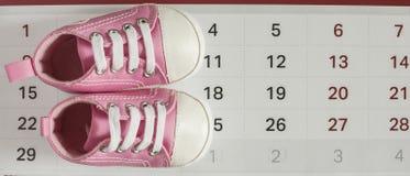 Behandla som ett barn lite skor med kalendern Royaltyfria Foton