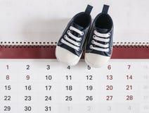 Behandla som ett barn lite skor med kalendern Royaltyfria Bilder