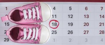 Behandla som ett barn lite skor med kalendern Fotografering för Bildbyråer