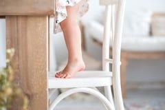 Behandla som ett barn liten fot, fot på en vit träköksstol i lantlig stil, en vind Arkivfoton