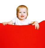 Behandla som ett barn lyckliga små för stående på den röda fåtöljen Royaltyfri Bild