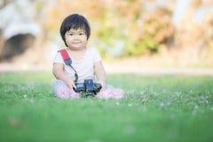Behandla som ett barn lyckligt fotografi och spela i trädgård Arkivbilder