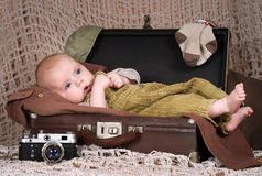 Behandla som ett barn (3,5 månader) lögner i retro-resväskan Royaltyfria Bilder