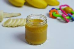 Behandla som ett barn mat, bananen mosade potatisar och bananer på en vit bakgrund som den isoleras Fotografering för Bildbyråer