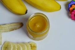 Behandla som ett barn mat, bananen mosade potatisar och bananer på en vit bakgrund som den isoleras Arkivfoton