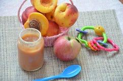 Behandla som ett barn mat, behandla som ett barn frukt som mosas i en glass krus, persikan, härliga persikor i en korg, leksak fö Royaltyfria Foton