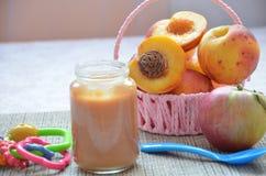 Behandla som ett barn mat, behandla som ett barn frukt som mosas i en glass krus, persikan, härliga persikor i en korg, leksak fö Royaltyfri Bild