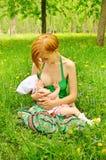 behandla som ett barn mata henne modern Royaltyfria Foton