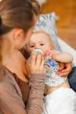 behandla som ett barn mata henne modern Arkivfoton