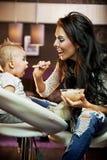 behandla som ett barn mata henne mumen Arkivbild