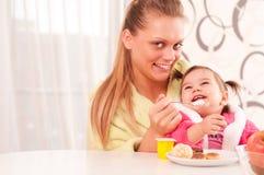behandla som ett barn mata henne ståendekvinnabarn Royaltyfri Fotografi