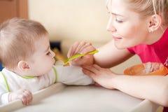 behandla som ett barn mata henne ståendekvinnabarn Arkivfoto
