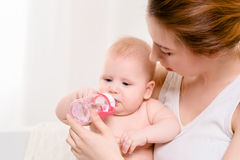 behandla som ett barn matning Behandla som ett barn att äta mjölkar från flaskan Arkivbilder