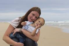 Behandla som ett barn med den lyckliga modern på stranden arkivfoto