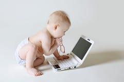 Behandla som ett barn med en bärbar dator Arkivbild