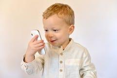 Behandla som ett barn med en mobiltelefon royaltyfria foton