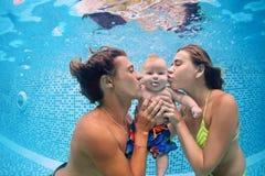 Behandla som ett barn med föräldrar lär att simma undervattens- i simbassäng Arkivfoto