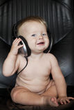 Behandla som ett barn med hörlurar på fåtöljen Arkivbilder