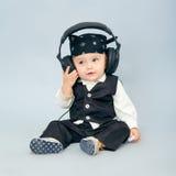 Behandla som ett barn med headphonen Arkivbild