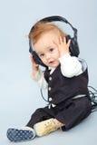 Behandla som ett barn med headphonen Arkivfoton