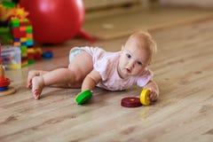 Behandla som ett barn med leksaker på golvet Arkivbilder