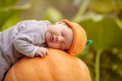 Behandla som ett barn med pumpahatten som sover på stor orange pumpa Royaltyfri Foto