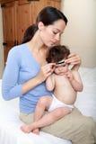 behandla som ett barn modern som tar temperatur Royaltyfri Foto