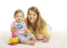 Behandla som ett barn modern, ungen som spelar kvarterleksaken, den unga familjen och barnet Fotografering för Bildbyråer