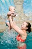 behandla som ett barn moderpölsimning Arkivfoto