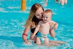 behandla som ett barn moderpölsimning Föräldern och barnet simmar i en tropisk semesterort Utomhus- aktivitet för sommar för fami royaltyfri bild