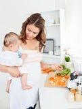 behandla som ett barn morötter henne holdingmodern som förbereder barn Arkivfoton