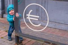 Behandla som ett barn nära valutautbyteskontoret Royaltyfri Foto