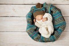 Behandla som ett barn nyfött sova i woolen hatt på vitt trä Royaltyfri Bild
