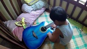 behandla som ett barn nyfiken årig pys 2 och att klinka gitarren på lathunden lager videofilmer
