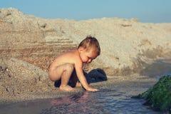behandla som ett barn nyfiket leka vatten för pojken Arkivfoto